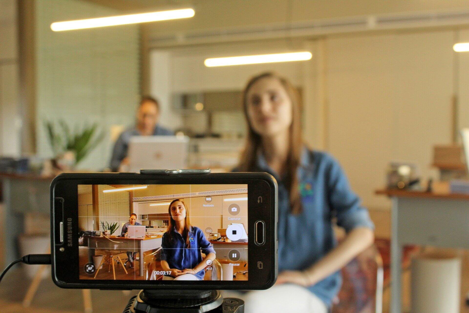 Frau vor und im Smartphone beim Filmen